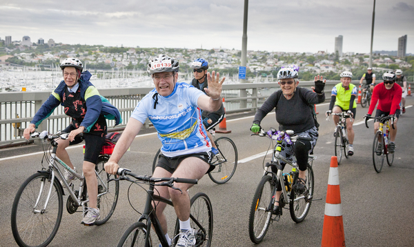 Auckland Mayor Len Brown riding over the crest of the Auckland Harbour Bridge.