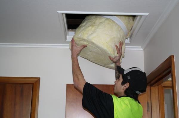Adam Fletcher from Bay Insulation 2007 Ltd passes blanket insulation into the ceiling of a unit in the Tui Vale complex.