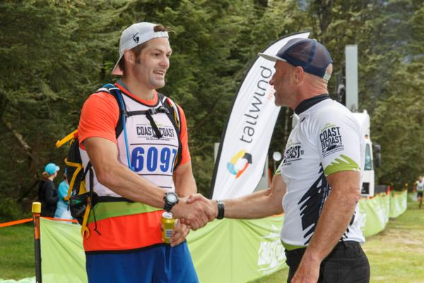 Richie McCaw is welcomed at the finish of the Coast to Coast mountain run by Kathmandu Coast to Coast nine time winner and ambassador Steve Gurney.