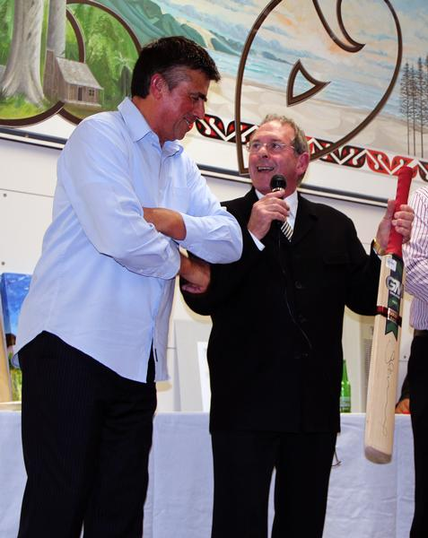 A cricket bat signed by Stephen Fleming and donated by Monty Knight, right, was auctioned for $420.