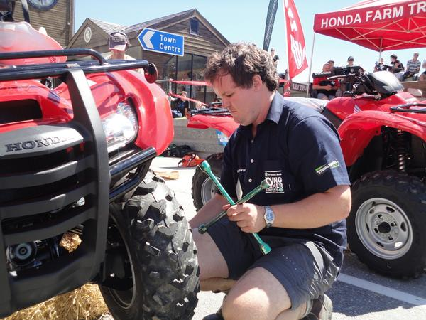 Michael Lilley fits a wheel to an ATV during a Practical Day Challenge.