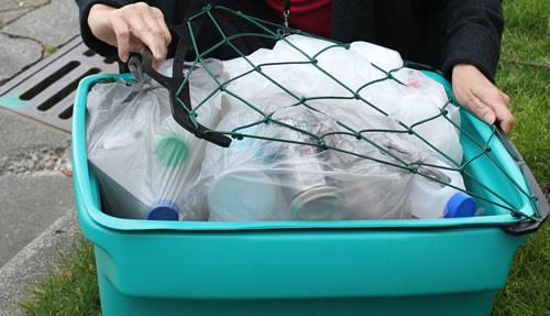 Flexible net designed to prevent the contents of recycling bins blowing away in the wind.