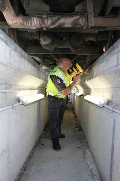 A Police Vehicle Safety Officer (VSO) ý a qualified mechanic ý conducts a safety check from the inspection pit at Glasnevin compliance station